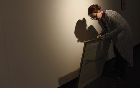 Alison Erazmus, the University Museum's curator of exhibits, examines the frame on a painting Wednesday, Jan. 18, 2017, in the museum. (Bill Lukitsch | @lukitsbill)