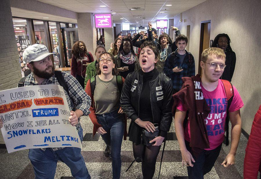 Thomas Birch, left, a junior who did not wish to disclose any additional information, marches in support of President Donald Trump alongside demonstrators Elena Cruz, a junior from Crystal Lake studying sociology, and Aster Arseneau, a sophomore from Carbondale, on Friday, Jan. 20, 2017, in the Student Center during a protest of Trump's inauguration.