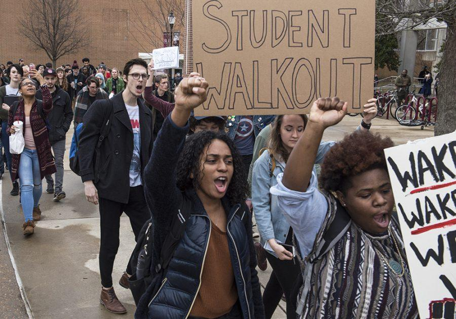 Re'Jean Pink, a freshman from Chicago studying English, left, and Jacquiese Robinson, a freshman from Chicago studying mortuary science and funeral service, raise their fists while marching around campus Friday, Jan. 20, 2017, during a student walkout event protesting President Donald Trump's inauguration.