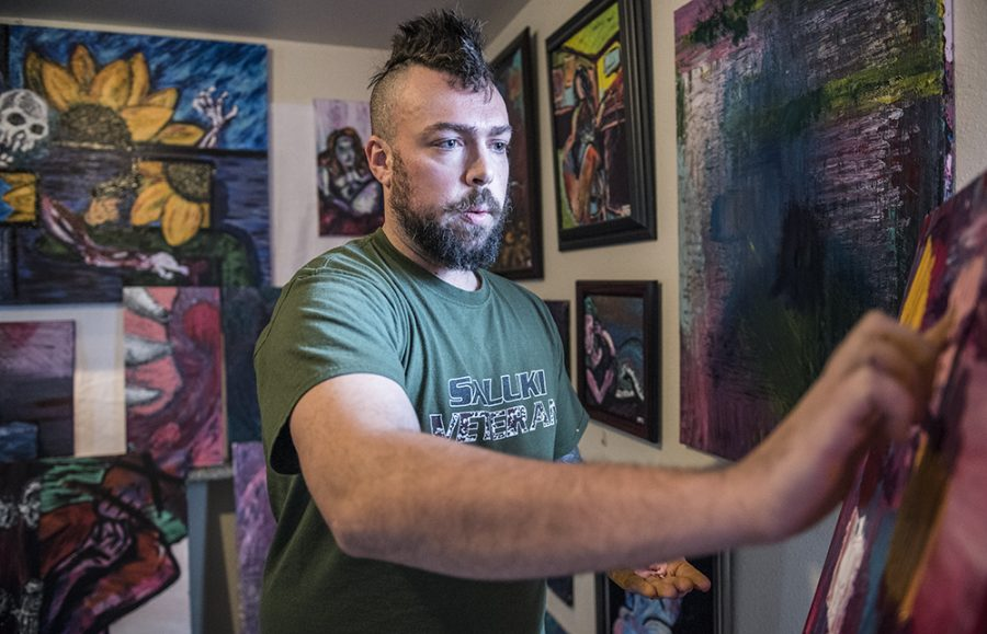 "In a living room filled with his artwork, Joshua-Kyle ""JK"" Brandon, a senior from Buffalo Grove studying psychology, finger paints Tuesday, Jan. 31, 2017, between classes in Carbondale. The Marine veteran sought out SIU's Counselling and Psychological Services after the deaths of his family members and a suicide attempt last year. ""[My counselor] helped me ground myself and reminded me that, as a human being, I need to honor all my feelings,"" Brandon said. ""I was liberated, it really changed me."" (Morgan Timms 