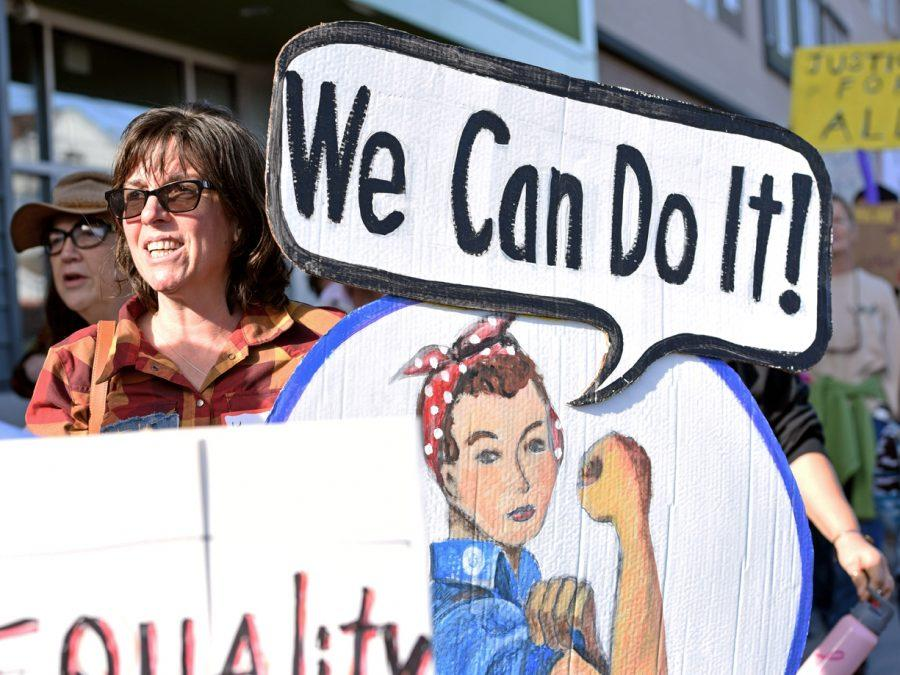 Kayeleigh Sharp, a doctoral candidate in anthropology from Denver, holds a Rosie the Riveter sign Saturday, Jan. 21, 2017, as she walks with other Southern Illinois Women's March participants down South Illinois Avenue. She said not one specific reason brought her out to the march, but instead some of everything, including her desire for SIU to become a santuary campus. (Anna Spoerre | @annaspoerre)