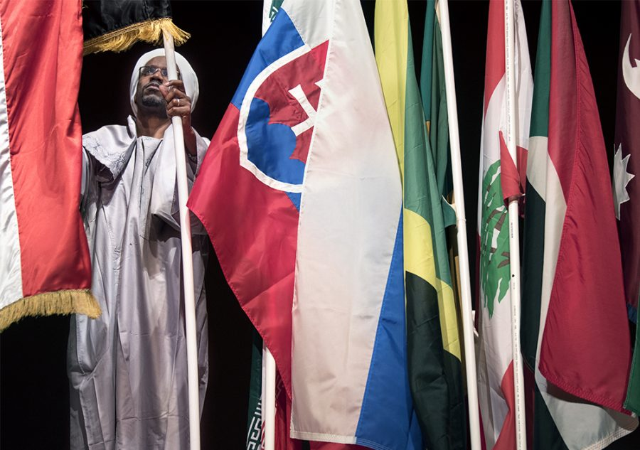 Omer Elsanusi, a Ph.D. candidate in mechanical engineering from Khartoum, Sudan, arranges flags from more than 30 different countries Monday, Feb. 6, 2017, after the annual International Parade of Flags in the Student Center ballroom. Elsanusi and his wife, Asia Abobaker, marched with their country's flag during the parade. Sudan was one of the seven countries banned from the United States in President Donald Trump's recent executive orders.