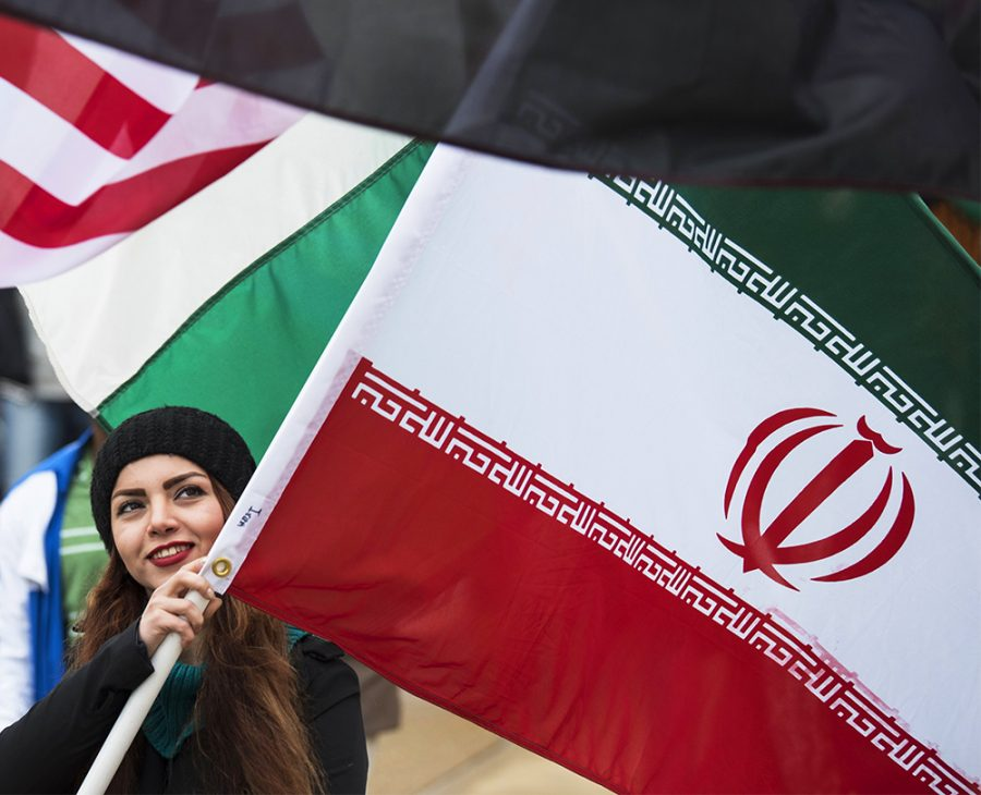 Azadeh Amiri, a graduate student in mechanical engineering from Tehran, Iran, marches with her country's flag Monday, Feb. 6, 2017, during the International Parade of Flags from Woody Hall to the Student Center.