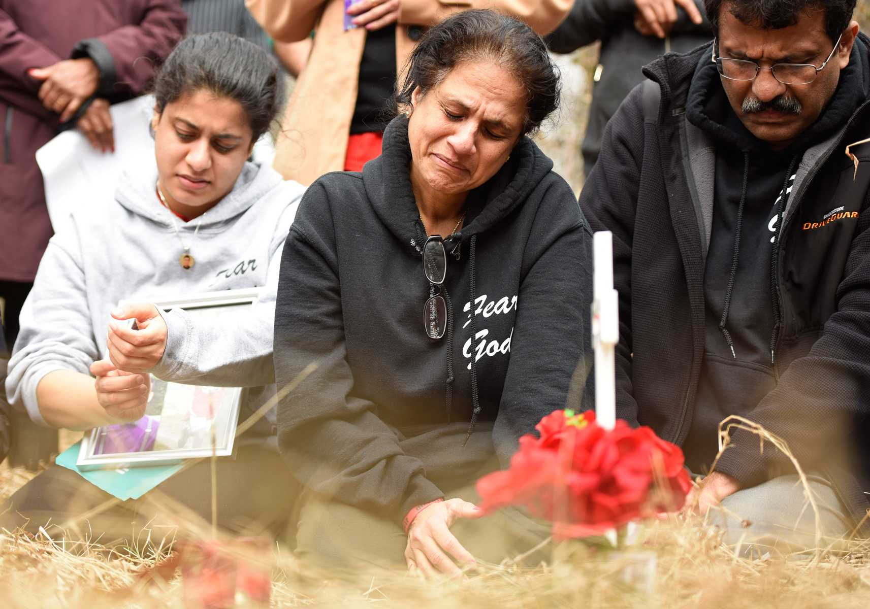 Pravin Varughese's older sister Priya, his mother Lovely, and his father Mathew kneel during a memorial ceremony on Saturday, Feb. 13, 2017, in the woods bordering Illinois Route 13, where police say he died of hypothermia about three years ago. (Luke Nozicka | @lukenozicka)