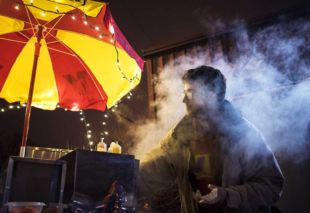 Chris Weatherwax, co-owner of Saluki Dawgs, battles the steam escaping from inside his hot dog cooker while preparing one of his specialty hot dogs for a customer Saturday, Feb. 18, 2017, by Pagliai's Pizza on the Strip. Weatherwax and his friend Thomas Becker began the business in December and serve customers between 11 p.m. and 2:30 a.m. Fridays and Saturdays. Weatherwax credits Saluki Ventures, part of the Office of Economic and Regional Development, with helping them start and maintain their business.