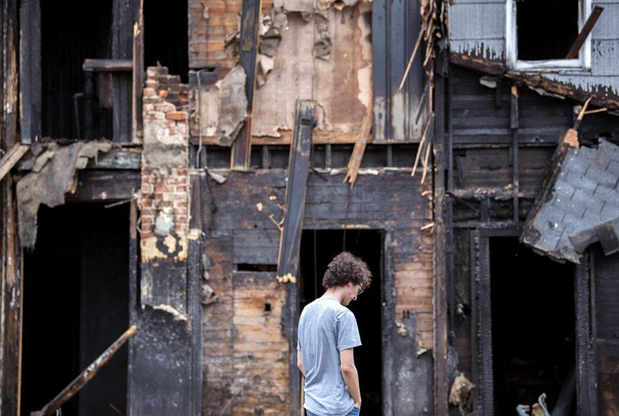 "John Kenny, a senior from Aurora studying political science, stands outside his former home for one of the last times Feb. 23 before Dustin Wheetley, of Wheetley Construction, returns to continue tearing down the burnt Carbondale building. A structure fire engulfed the house on Nov. 23 and killed Kenny's 20-year-old roommate, Alex Kierstead. ""I can remember us all sitting in [that living room] not too long ago,"" Kenny said. ""I want to say that coming here to see [the house] is kind of a bit of closure, but it's not really. It's still an open wound. … A part of me wants to say good riddance to it all, but a part of me is just kind of numb. It's almost better that way."""