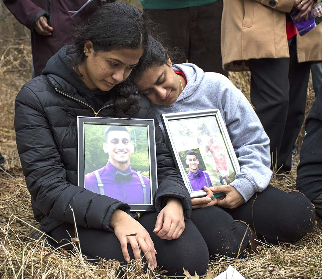 From left to right: Pravin Varughese's younger sisters  Preethi and Priya kneel during a memorial ceremony Saturday, Feb. 11, 2017, in a wooded area bordering Illinois Route 13 where police say Pravin died of hypothermia, three years ago.