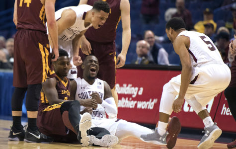 Saluki sophomore guard Sean Lloyd, on ground, celebrates with junior guard Jonathan Wiley and senior guard Leo Vincent (5) after corralling a loose ball Friday, March 3, 2017, during the Salukis' 55-50 win against Loyola in the Missouri Valley Conference men's basketball tournament quarterfinals at Scottrade Center in St. Louis. (Sean Carley | @SeanMCarley)
