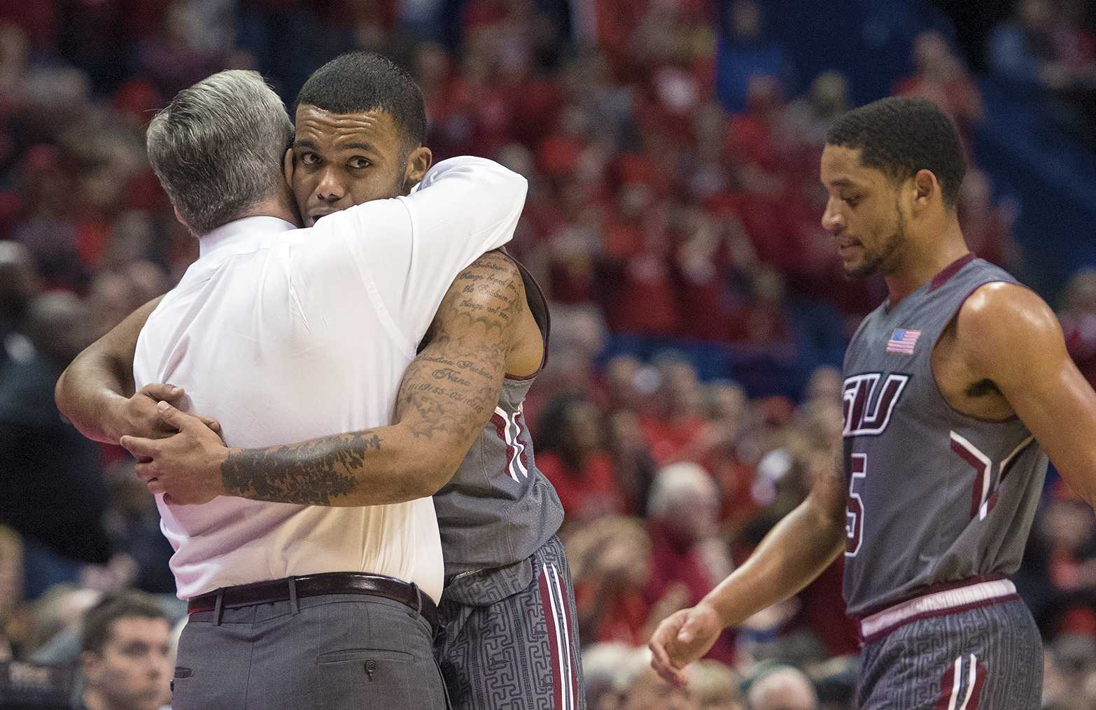Coach Barry Hinson hugs senior guard Mike Rodriguez as he and fellow senior guard Leo Vincent walk off the floor for the last time in their Saluki careers Saturday, March 4, 2017, during SIU's 63-50 loss to Illinois State in the Missouri Valley Conference men's basketball tournament semifinals at Scottrade Center in St. Louis. (Sean Carley | @SeanMCarley)
