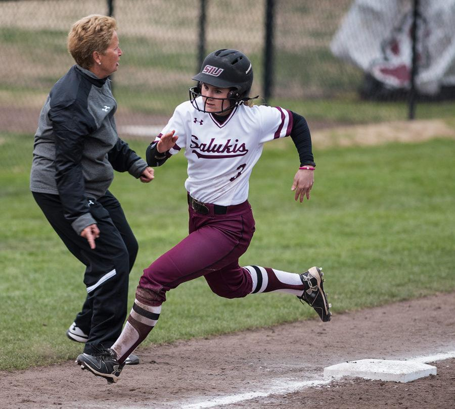 Freshman outfielder Susie Baranski rounds third as coach Kerri Blaylock signals during SIU's 9-3 loss to the Northern Illinois Huskies on Sunday, March 5, 2017, at Charlotte West Stadium. (Jacob Wiegand | @jawiegandphoto)