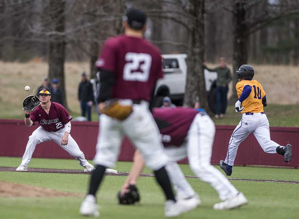 Junior first baseman Logan Blackfan catches a throw from senior third baseman Ryan Sabo as Western Illinois junior infielder Mitch Ellis approaches first base Sunday, March 5, 2017, at Itchy Jones Stadium. The Salukis beat the Leathernecks 3-2. (Branda Mitchell | @branda_mitchell)