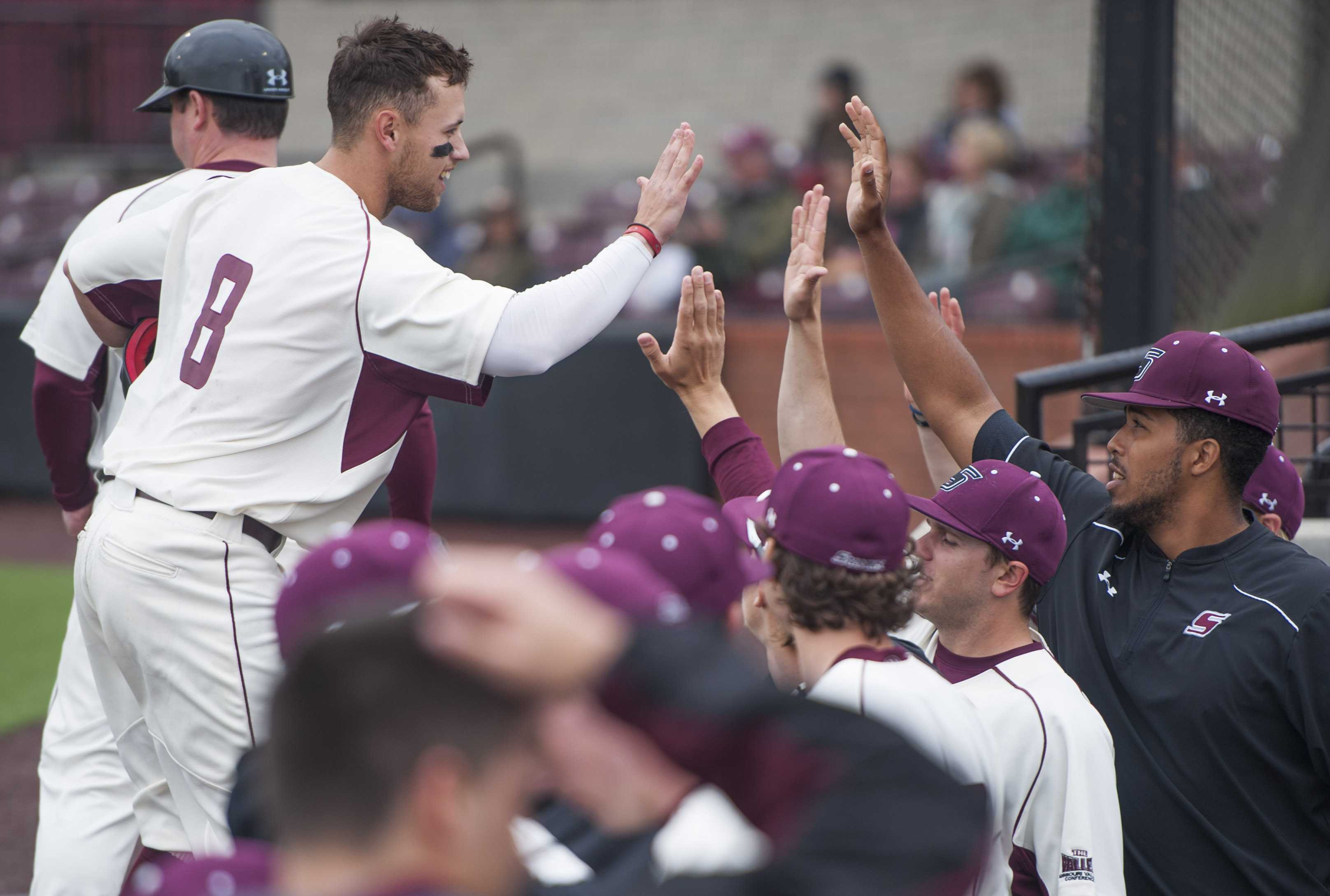 Senior outfielder Jake Hand high-fives teammates in the bullpen Saturday, March 25, 2017, after scoring a run against the Jacksonville State Gamecocks. The Salukis beat the Gamecocks 5-4 during the second of a three-game series at Itchy Jones Stadium. (Bill Lukitsch | @lukitsbill)