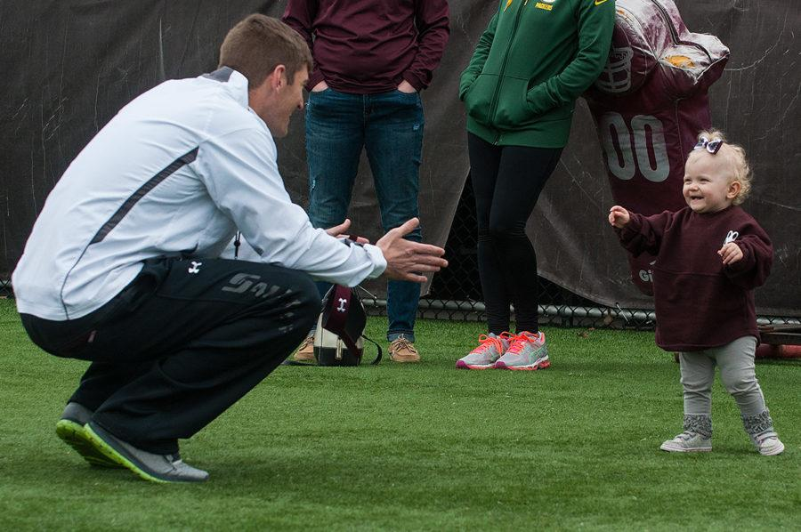 Coach Nick Hill extends his arms to his daughter, Skylar Jo Hill, 1, on Sunday, March 26, 2017, after SIU football's first spring scrimmage of the season at Saluki Stadium. Skylar was born in February 2016 — a month after her father's appointment as SIU's head coach. (Jacob Wiegand   @jawiegandphoto)