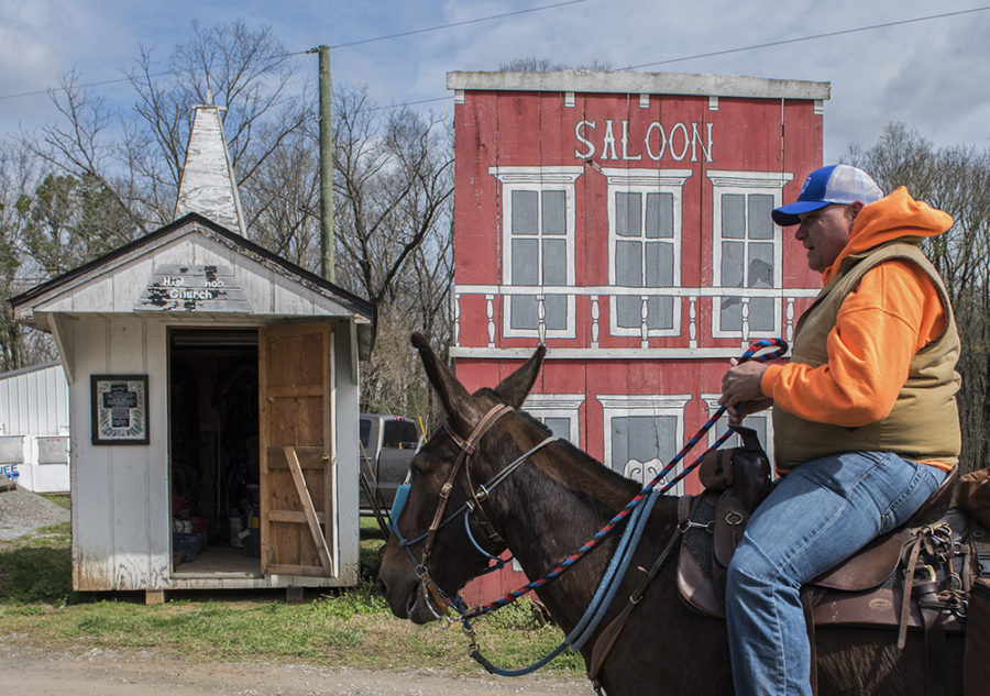 Donnie Murray, of Livermore, Kentucky, rides his mule passed old church and saloon props before beginning the morning's trails Thursday, April 6, 2017, during the second annual McAllister and Friends Mule Ride at High Knob Campground in the Shawnee National Forest. (Morgan Timms | @Morgan_Timms)