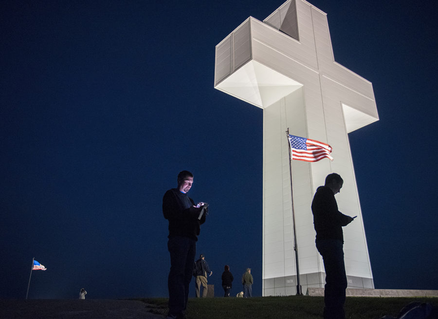 Spectators check their phones Sunday, April 16, 2017, before the start of the 81stannual Easter sunrise service at the Bald Knob Cross of Peace in Alto Pass. (Morgan Timms | @Morgan_Timms)
