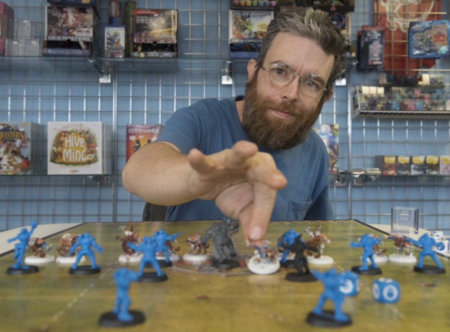 James Cox, owner of The Game Table, poses for a portrait with the game Blood Bowl, a fantasy football board game Monday, April 17, 2017, inside his store. Cox opened the store at 606 S. Illinois Ave. in April after working at Castle Perilous Games and Books in Carbondale for two years. The store sells a variety of board games and hosts weekly competitions with games like Dungeons & Dragons, Warhammer and Pokémon. (Bill Lukitsch | @lukitsbill)