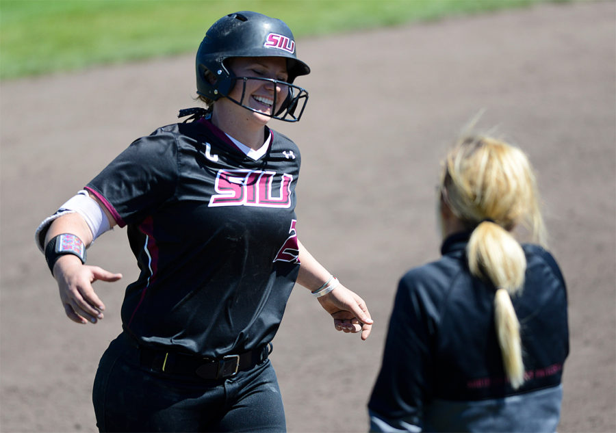Senior first baseman Shaye Harre reaches to high-five assistant coach Jen Sewell after her three-run home run in the sixth inning of the second game of SIU's doubleheader with Wichita State on Sunday, April 23, 2017 at Charlotte West Stadium in Carbondale. The Salukis won the game 5-4. (Sean Carley | @SeanMCarley)