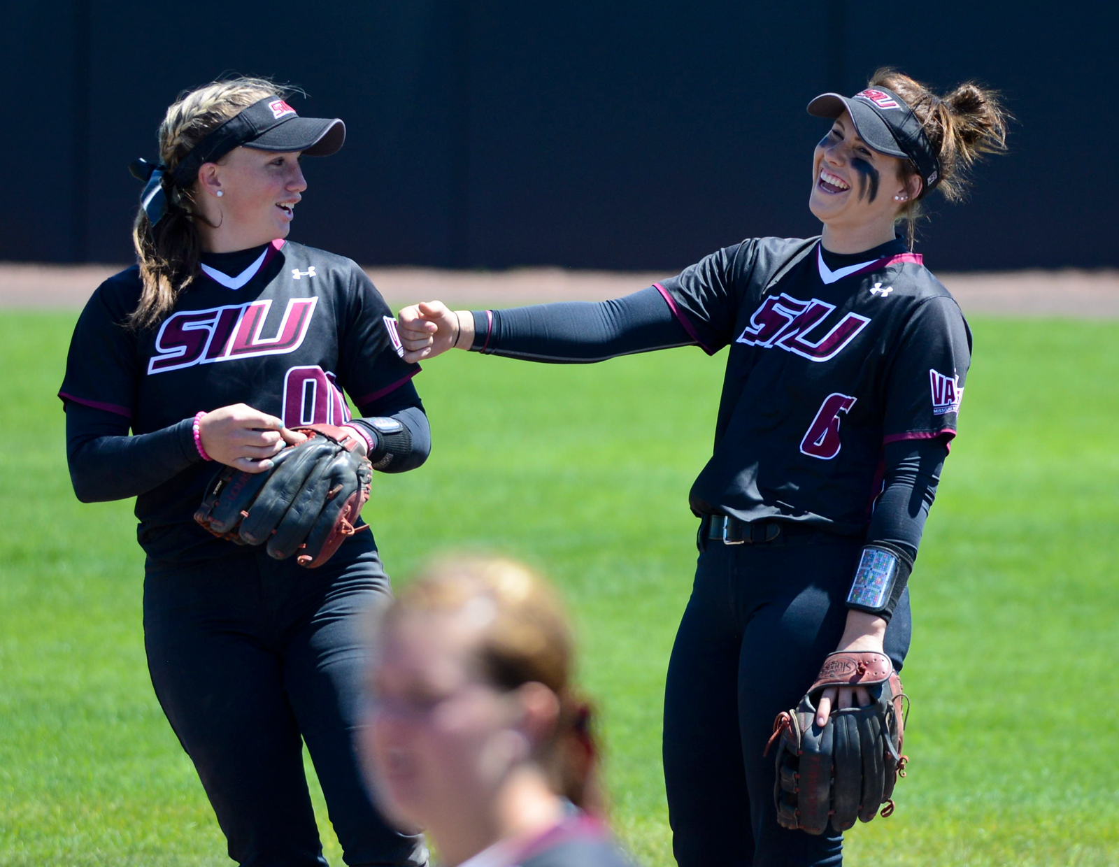 Junior third baseman Sydney Jones (left) and junior shortstop Savannah Fisher joke around before an inning during the second game of SIU's doubleheader with Wichita State on Sunday, April 23, 2017 at Charlotte West Stadium in Carbondale. The Salukis won the game 5-4. (Sean Carley | @SeanMCarley)