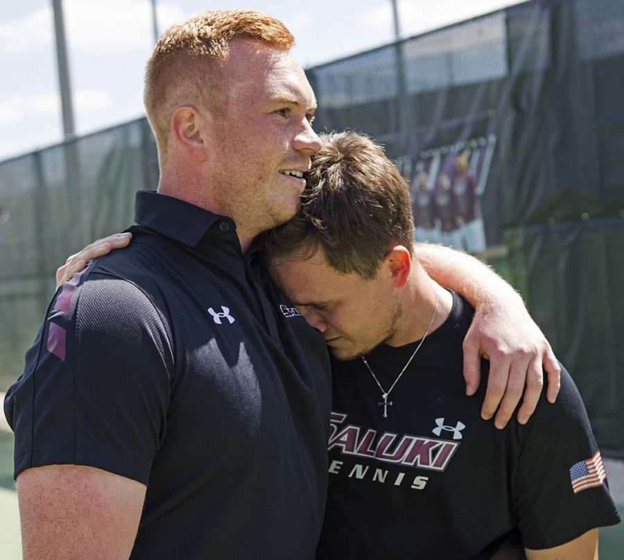 SIU men's tennis graduate assistant coach Jonny Rigby comforts junior Daniel Martinez after the Salukis beat Wichita State 4-1 on Saturday, April 1, 2017, in the last home match in Saluki men's tennis history at University Courts. (Athena Chrysanthou | @Chrysant1Athena)
