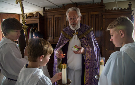 Monsignor Ken Schaefer lights the candle of Braden Burris, of Energy, while Johnston City resident Blake Gualdoni, with cross, and Gavin Shramm, of Herrin, observe prior to a Lenten ceremony of Stations of the Cross on Friday, March 24, 2017, at Our Lady of Mount Carmel in Herrin. Born in Belleville and raised in the St. Clair County village of Millstadt, Schaefer was ordained a priest on June 8, 1974. The priest has presided over the southern Illinois parish since 1994. (Jacob Wiegand | @jawiegandphoto)