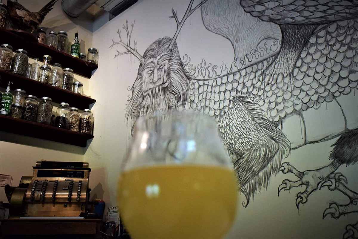 A mural of the Piasa Bird, a Native American dragon most likely from the Cahokian civilization, is seen behind a glass of Lemongrass Sorghum Saison beer on Saturday, April 29, 2017, at Scratch Brewing Company in Ava. The drawing is based off a modern interpretation of the original. (Joseph McLaughlin   @jmcl_DE)