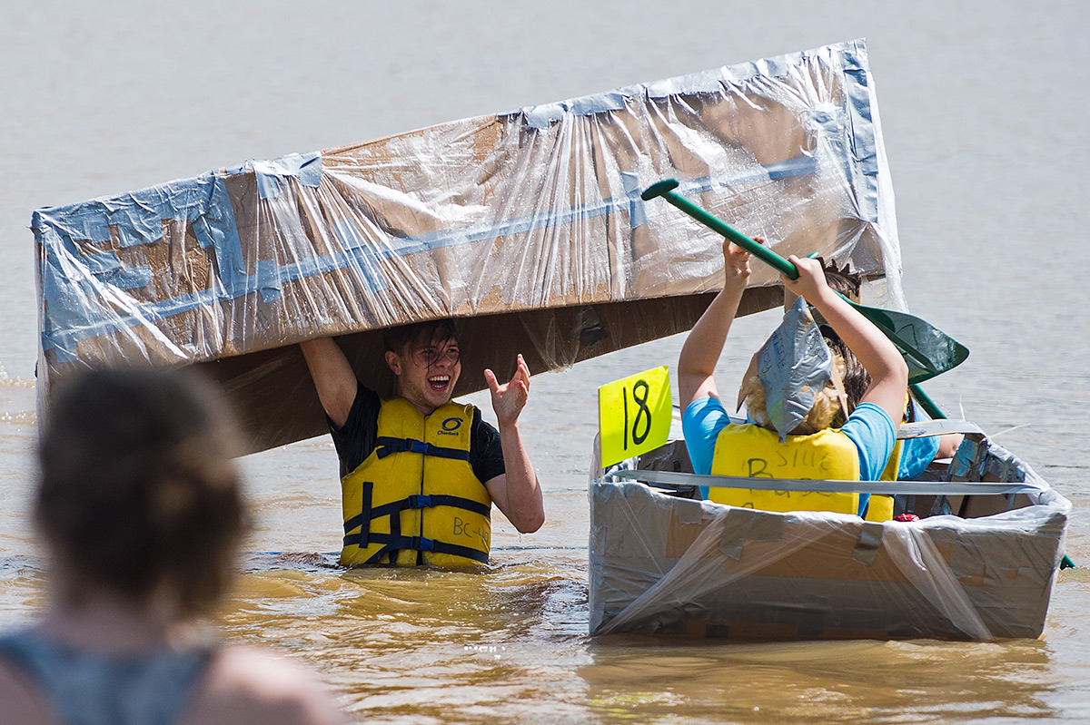 Gianluca Peter, 18, of Frankfurt, Germany, shares a moment with 14-year-old Alicia Martinez, of Málaga, Spain, and 15-year-old Berget Borowitz, of Carbondale, after the capsizing of Peter's boat, The Chuckles, on Saturday, May 6, 2017, during the 44th Annual Great Cardboard Boat Regatta at Evergreen Park in Carbondale. (Jacob Wiegand | @jawiegandphoto)