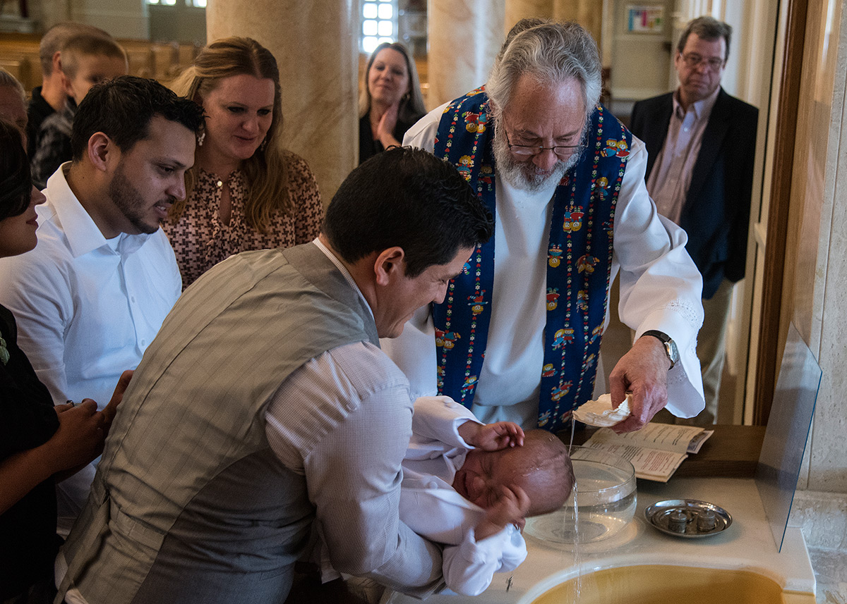Monsignor+Ken+Schaefer+baptizes+1-year-old+Luka+Castillo%2C+of+Carterville%2C+as+he+is+held+by+his+father+Carlos+Castillo%2C+who+is+originally+from+Mexico+and+now+lives+in+Carterville%2C+on+Sunday%2C+April+2%2C+2017%2C+at+Our+Lady+of+Mount+Carmel+in+Herrin.+%28Jacob+Wiegand+%7C+%40jawiegandphoto%29