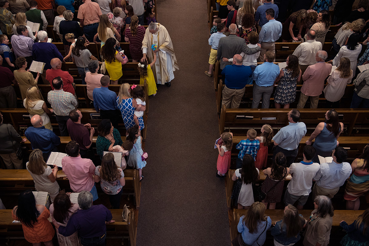 Monsignor+Ken+Schaefer+receives+a+bouquet+of+flowers+from+Sophie+El+Kajawaii-Louban%2C+a+Pre-K+student+at+OLMC%2C+as+the+monsignor+exits+the+church+at+the+conclusion+of+the+Easter+Sunday+masses+April+16%2C+2017%2C+at+Our+Lady+of+Mount+Carmel+in+Herrin.+Schaefer+said+he+enjoys+being+a+priest+because+of+the+effect+he+sees+in+the+lives+of+people.+%22In+ministry%2C+when+you+see+people+growing+in+their+faith%2C+it%27s+sort+of+like+a+parent+watching+their+child+start+walking+and+talking%2C%22+he+said.+%28Jacob+Wiegand+%7C+%40jawiegandphoto%29