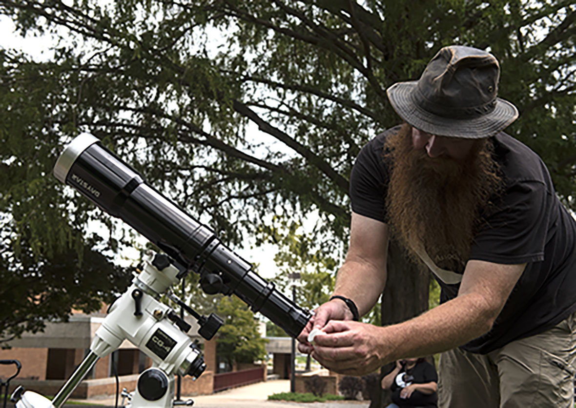 "Christopher Mandrell, a graduate student from Marion studying physics, takes apart an 80mm telescope Tuesday, Aug. 15, 2017, outside Neckers after a practice run aligning the telescope in preparation for the eclipse. Mandrell will camp out at the University Farms ""dark site"" the night before he the eclipse so he can set up for the experimental run the following day. ""This is the classic ... telescope,"" Mandrell said. ""It's a refraction scope just using the lenses to focus just like your glasses."" (Cory Ray 