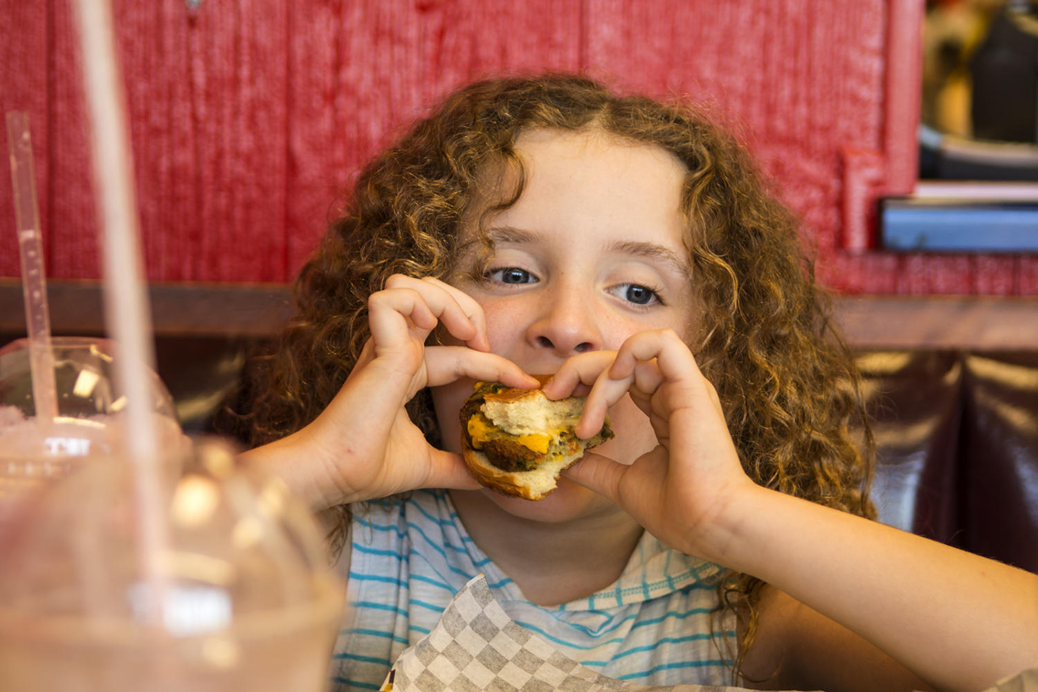 Megan Fakhoury, 7, of Carbondale, takes a bite out of a cheeseburger Saturday, Aug. 26, 2017, at Dale's Burgers in Carbondale. (Athena Chrysanthou | @Chrysant1Athena)