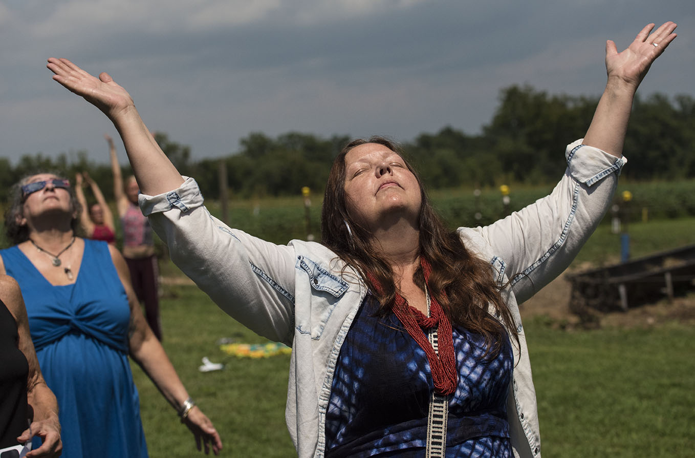 "Georgia De-La-Garza, of Cherokee, raises her hands into the sky Monday, Aug. 21, 2017, just after the solar eclipse at Dancing Willow Farm in Makanda. ""To me it means transformation,"" De-La-Garza said. ""Both of my children moved out so I am transforming into a single person again."" De-La-Garza said she has been mentally preparing for the eclipse for over a year. ""I think everyone had their own personal experience and I will continue to seek myself inward,"" De-La-Garza added. ""I hope everyone takes these moments that are given to us, hold them close and do a sort of reflection."" (Athena Chrysanthou 
