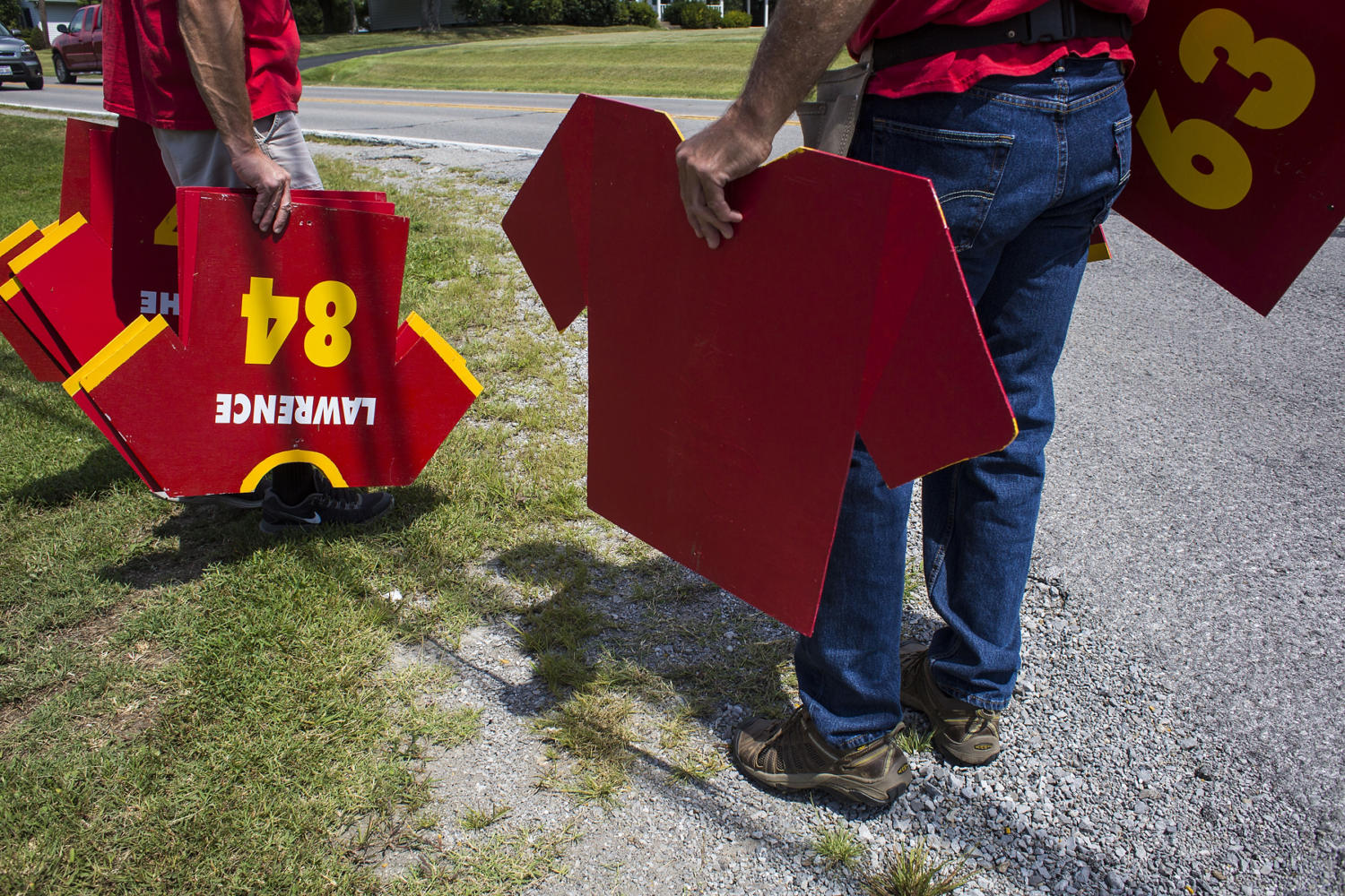 Grant Guthman, left, and Mike Karg, both of Murphysboro, hang Red Devils football jersey signs along North 14th Street prior to the 100th meeting between the Murphysboro Red Devils and the Carbondale Terriers on Friday, Aug. 25, 2017, in Murphysboro, Illinois. (Ryan Michalesko | @photosbylesko)