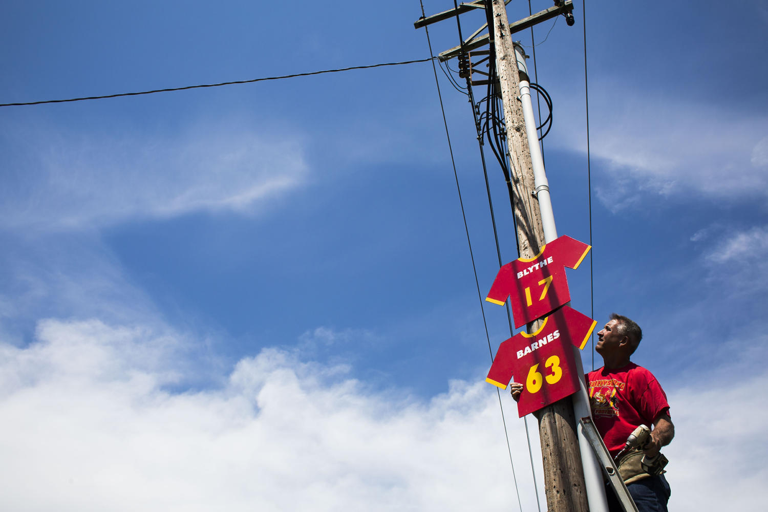 Mike Karg hangs Red Devils football jersey signs along North 14th Street prior to the 100th meeting between the Murphysboro Red Devils and the Carbondale Terriers on Friday, Aug. 25, 2017, in Murphysboro, Illinois. (Ryan Michalesko | @photosbylesko)