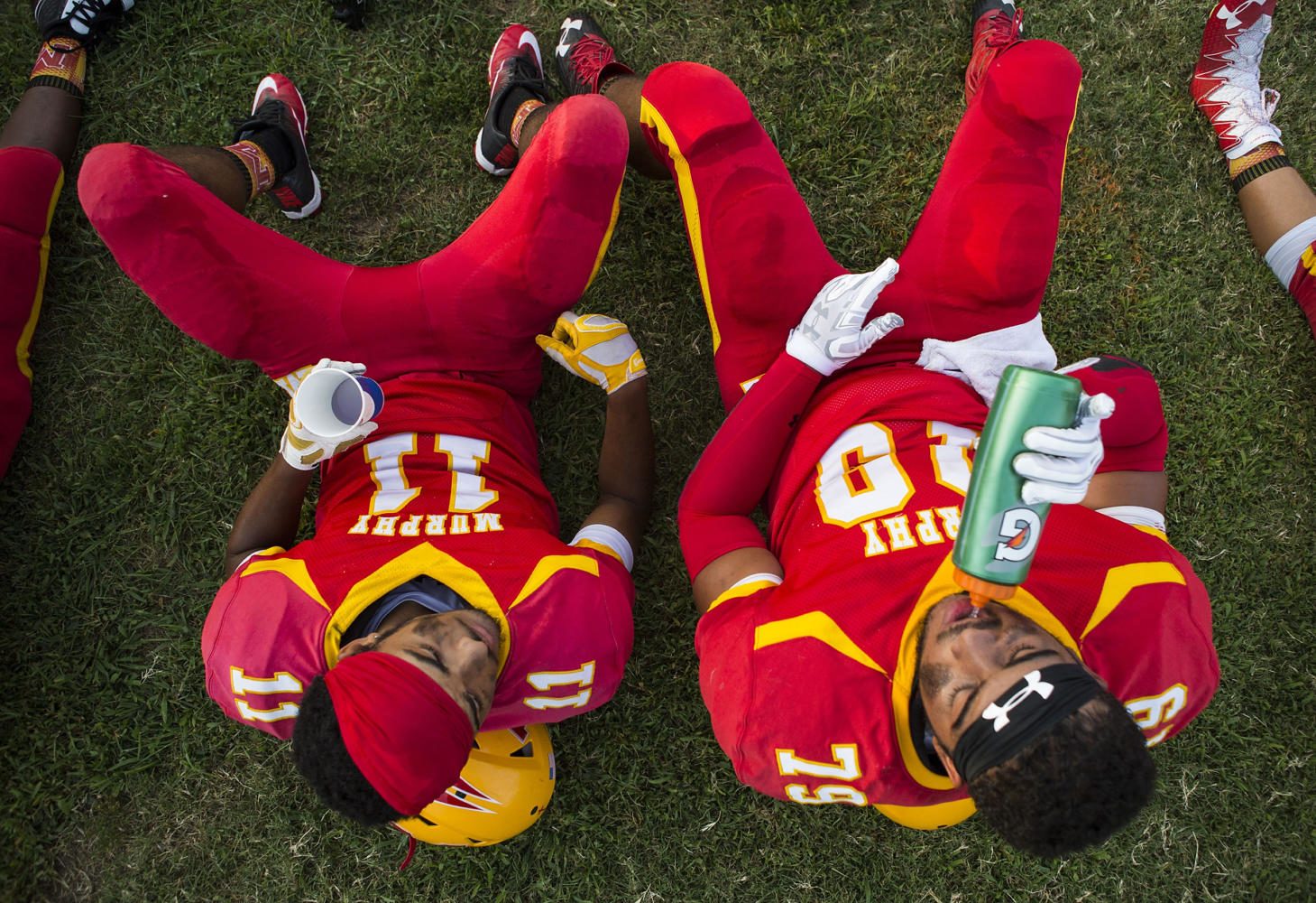 Murphysboro quarterback Gavin Topp, left, and outside linebacker Mo Valliant rest prior to kickoff of the 100th meeting between the Murphysboro Red Devils and the Carbondale Terriers on Friday, Aug. 25, 2017, at