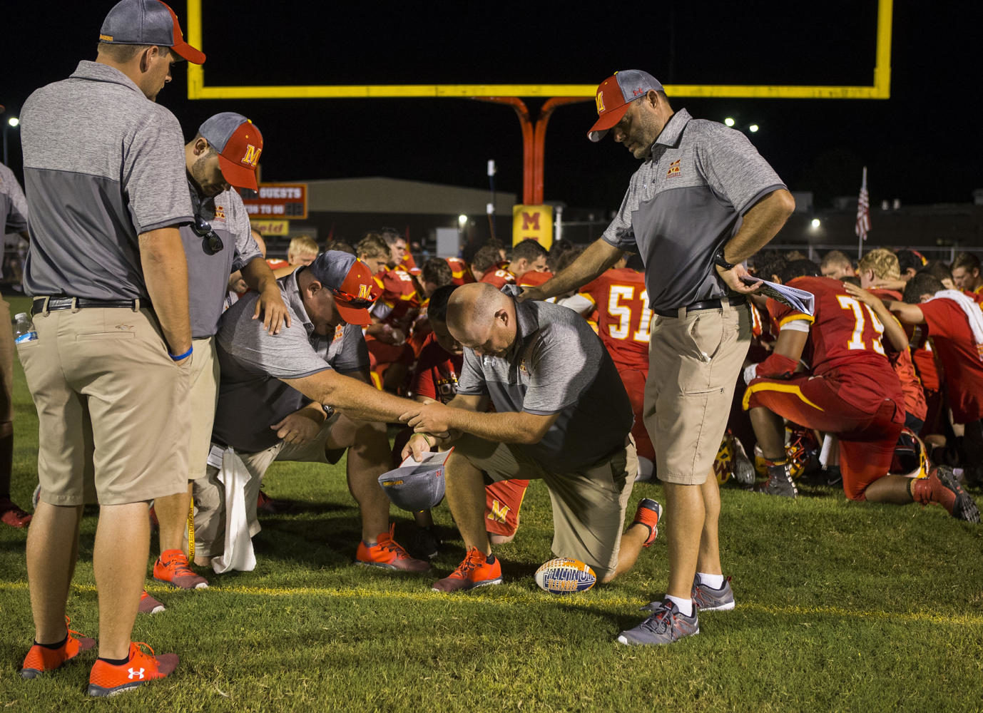The Red Devils coaching staff prays together after losing to the Carbondale Terriers in the the 100th meeting of the two teams on Friday, Aug. 25, 2017, at