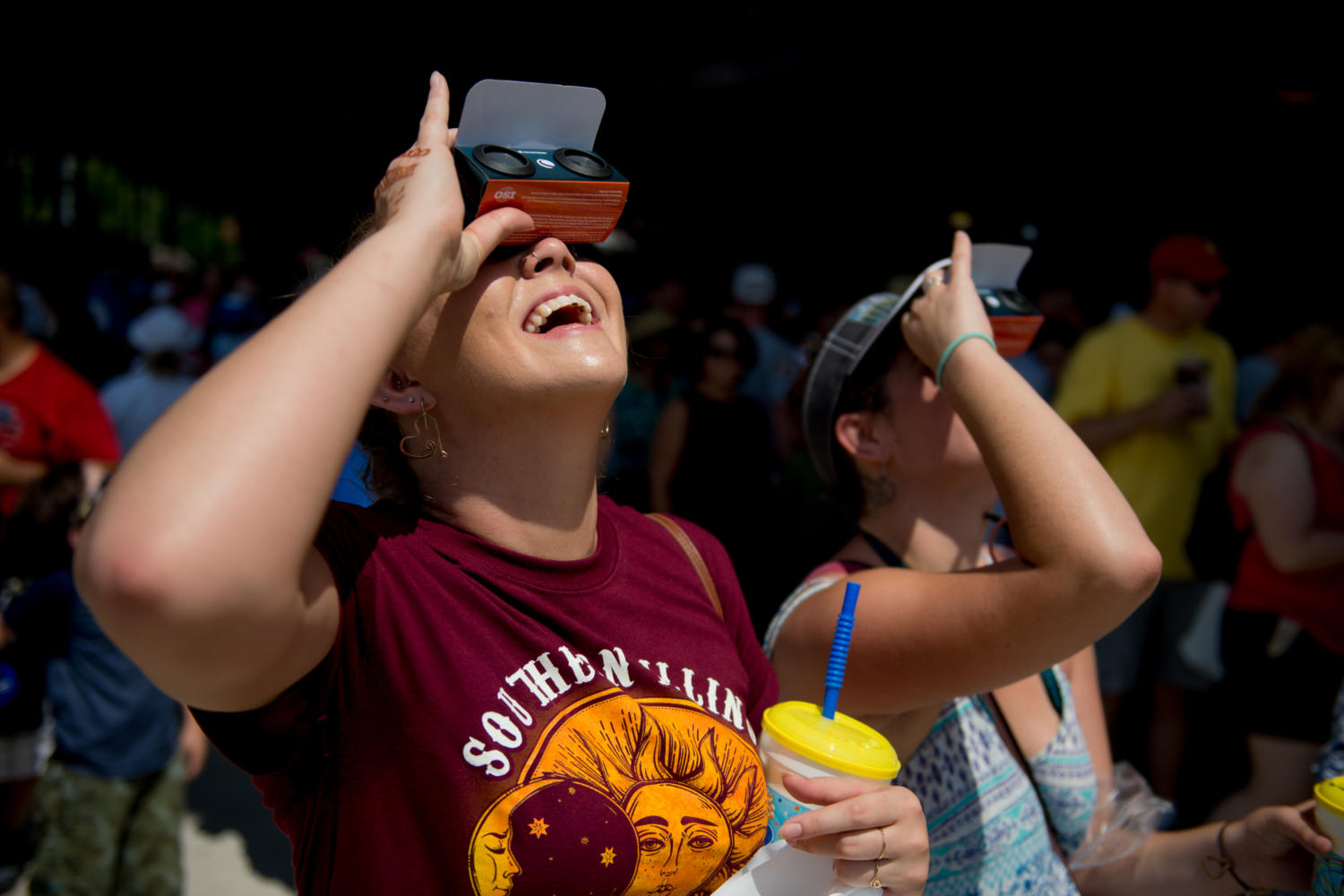 Susan Petrosky, of Springfield, watches the solar eclipse through special eclipse glasses Monday, Aug. 21, 2017, outside Saluki Stadium.