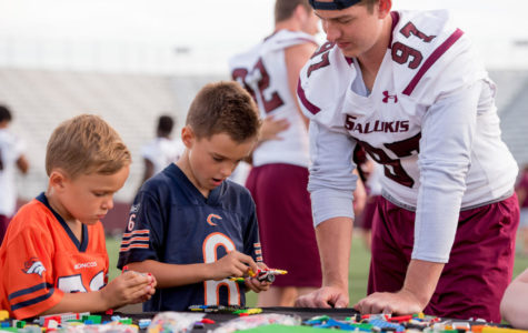 Drew Owens, left, and Lukas Owens, both of Carterville, play with redshirt freshman Sam Bonansinga Thursday, Aug. 24, 2017, during Fan Fest at Saluki Stadium. (Dylan Nelson | @DylanNelson99)