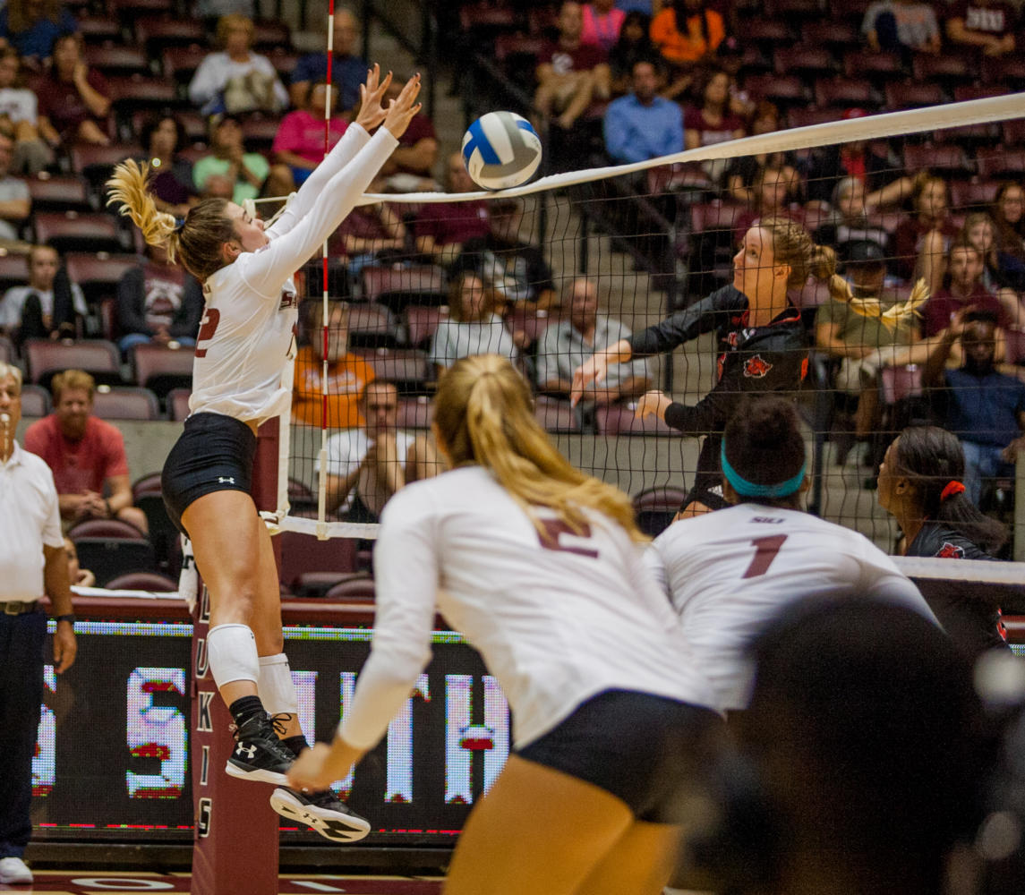 Sophomore outside hitter Alysa Sutton, 12, blocks the ball Tuesday, Aug. 29, 2017, during the Salukis' 22-25 loss against Arkansas State University at SIU Arena. (Mary Newman | @MaryNewmanDE)