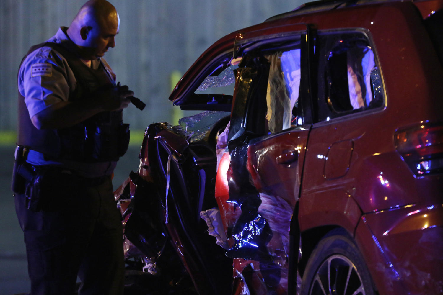 A police officer looks at one of the vehicles involved in a multi-vehicle crash in the 3700 block of West Roosevelt Road that followed a shooting on Saturday, July 8, 2017, in Chicago, Ill. At least three vehicles were involved in the crash, and at least six people were transported to area hospitals, including three gunshot victims. (John J. Kim/Chicago Tribune/TNS)