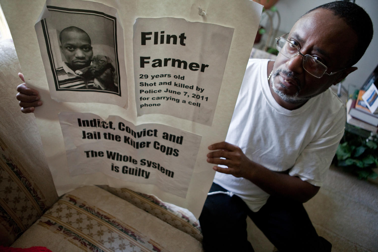 Emmett+Farmer%2C+51%2C+father+of+Flint+Farmer%2C+poses+for+portrait+with+a+poster+at+his+home+in+Sauk+Village%2C+Illinois%2C+October+21%2C+2011.+Flint+Farmer%2C+29%2C+was+unarmed+when+he+was+shot+and+killed+by+a+police+officer+in+June.+%28Zbigniew+Bzdak%2FChicago+Tribune%2FMCT%29