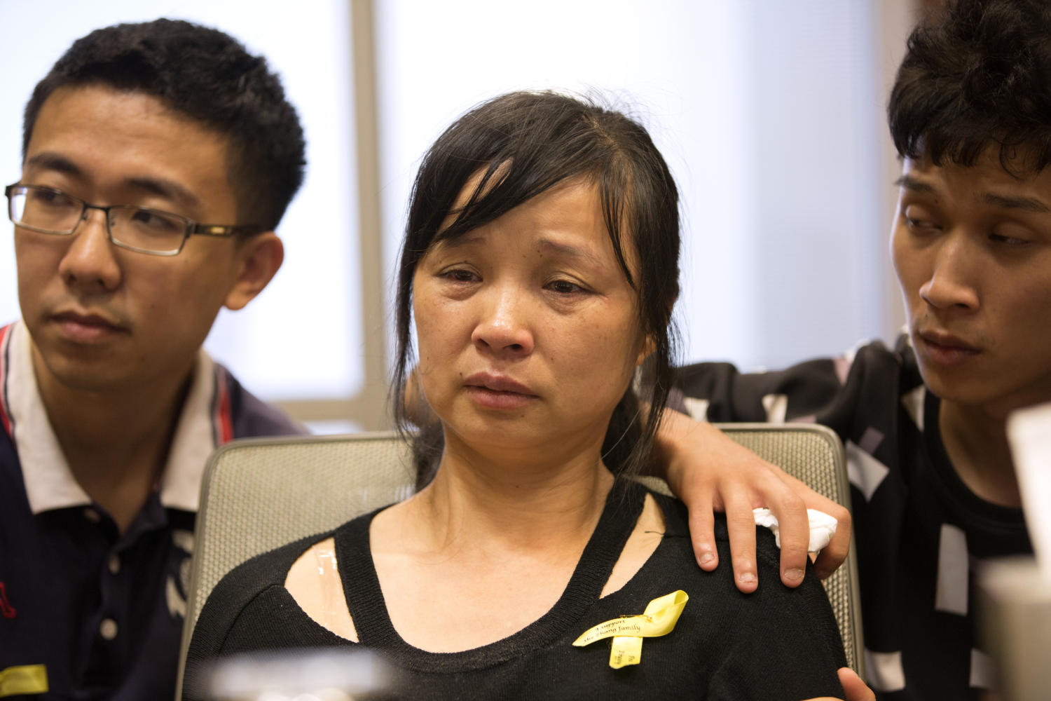 Lifeng Ye, mother of Yingying Zhang, a visiting scholar at the University of Illinois at Urbana-Champaign who authorities say was kidnapped near a bus stop on campus June 9, sits with her son Xinyang Zhang, right, and Xiaolin Hou, Yingying's boyfriend, after a news conference at the I Hotel and Conference Center in Champaign, Ill., on Tuesday, Aug. 22, 2017. (Erin Hooley/Chicago Tribune/TNS)