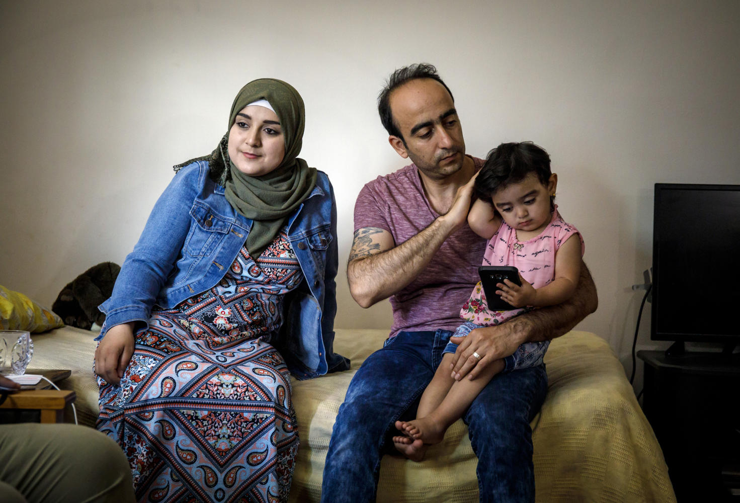 Baraa, Abdulmajeed and Sham Haj Khalaf sit in the living room of their Skokie, Ill. home on July 23, 2017. The family emigrated as refugees from Syria. (Brian Cassella/Chicago Tribune/TNS)