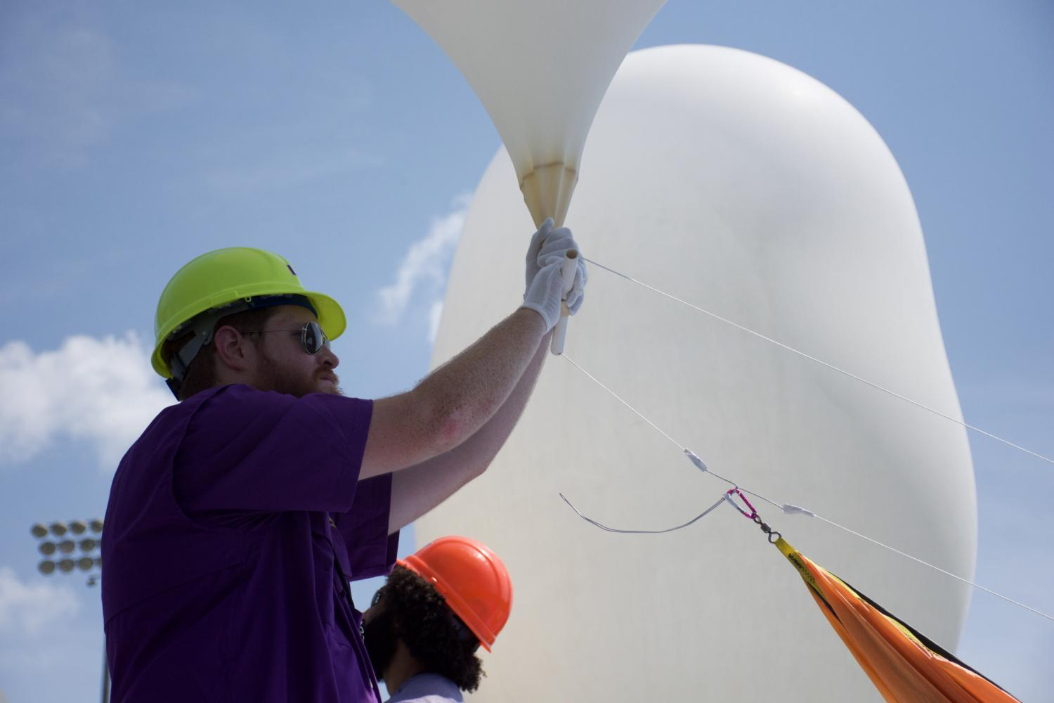 "Louisiana State University senior physics major Brad Landry holds a weather balloon carrying experiments from three different Louisiana colleges minutes before launch, Monday, Aug 21. 2017, at SIU Stadium. Landry released the balloon at 11:51 a.m. where it then traveled 100,000 feet into the sky with devices used to measure changes in solar power levels, UV radiation and the speed of sound. ""When we started college, we never expected to work on something like this,"