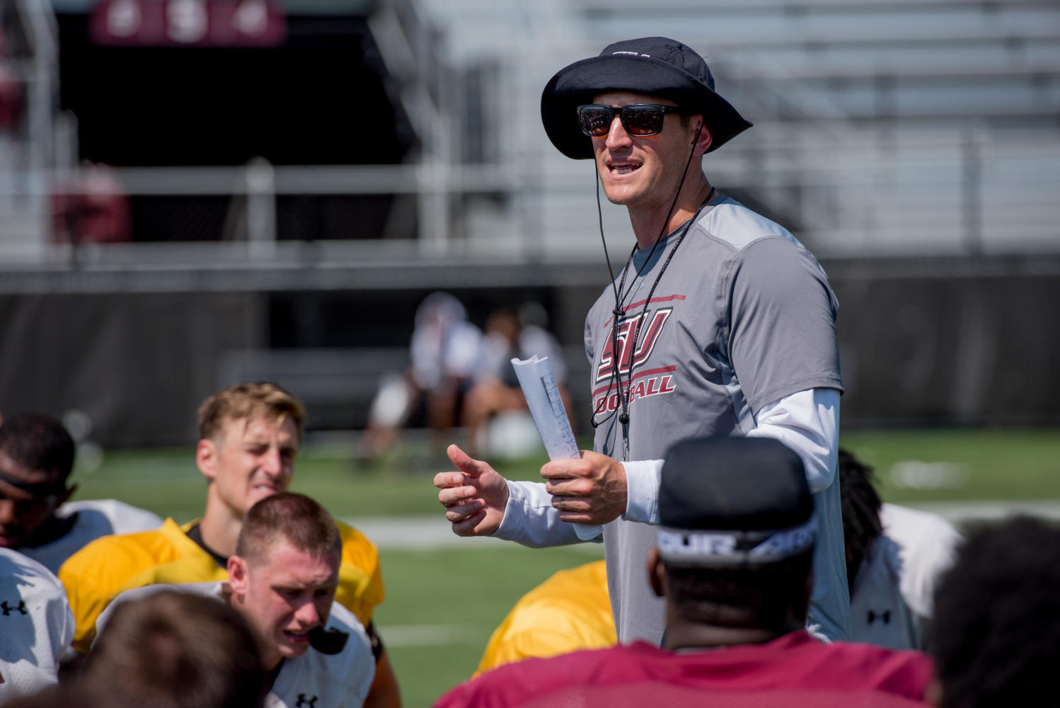 SIU Fooball head coach Nick Hill talks to members of the Saluki football team after their first fall scrimmage, Saturday, Aug. 11, 2017, at Saluki Stadium.