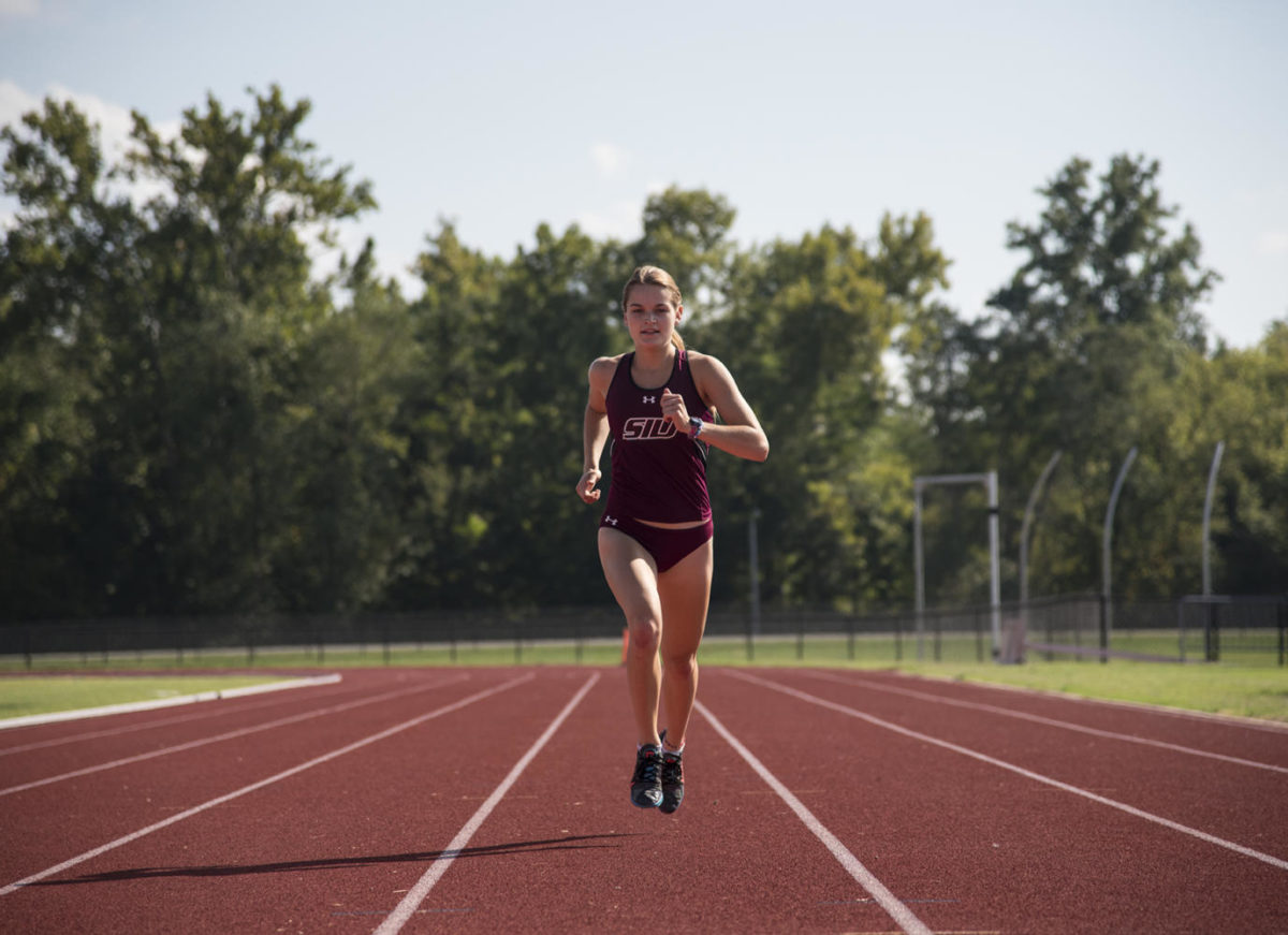 Junior cross country runner Megan Krolak runs Tuesday, Sept. 19, 2017, before practice at the Lew Hartzog Track and Field Complex. (Athena Chrysanthou | @Chrysant1Athena)