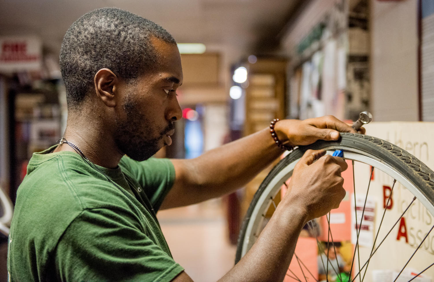 Darrien Moore, senior aviation major, of Blue Island, takes a wheel off of a student's bike Monday, Aug. 28, at Saluki Spokes in the Student Center. Saluki Spokes provides free to use tools in order to get students bicycles back up and running. (Dylan Nelson | @DylanNelson99)