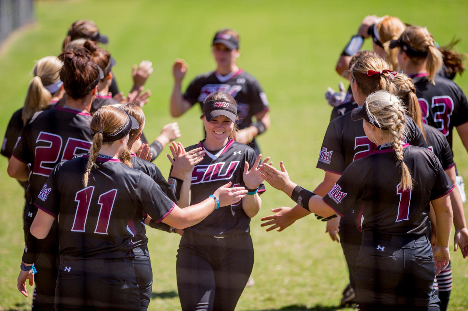 Sophomore outfielder Susie Baranski (center) high fives teammates Sunday, Sept. 10, 2017, before the start of their home opener against Rend Lake College at Brechtelsbauer Field. The Saluki Softball team returns to SIU after winning the 2017 Missouri Valley Conference championship. (Brian Muñoz | @BrianMMunoz)
