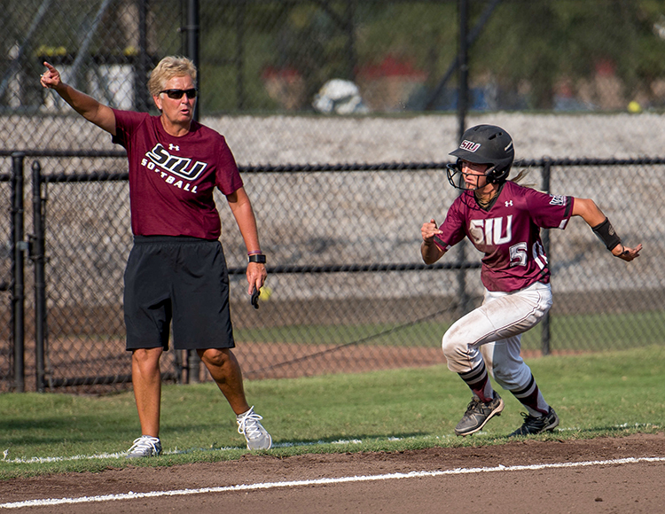 SIU coach Kerri Blaylock gestures as senior outfielder Brittany Turner  runs for home plate Saturday, Sept. 23, 2017, during a game against the UMSL Tritons at Charlotte West Stadium. (Auston Mahan | @AustonMahanDE)