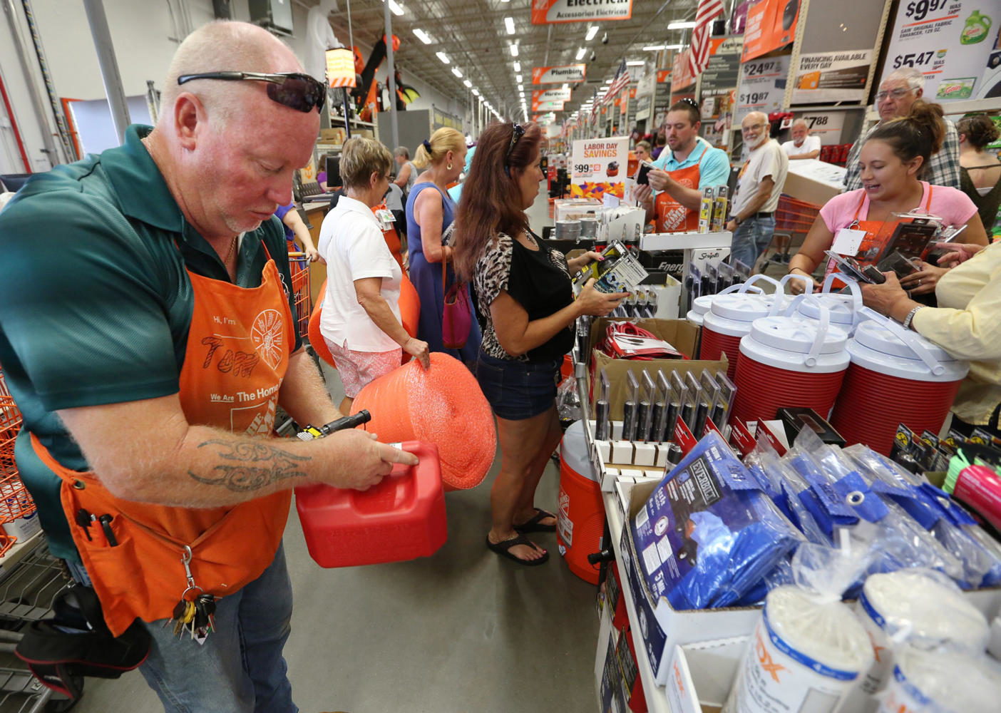 Tom Kepner, left, stocks gas containers as shoppers buy hurricane items at The Home Depot in Lady Lake on Tuesday afternoon, Sept. 5, 2017. Buyers are preparing for Hurricane Irma. The store was out of generators and water early Tuesday. (Stephen M. Dowell/Orlando Sentinel/TNS)