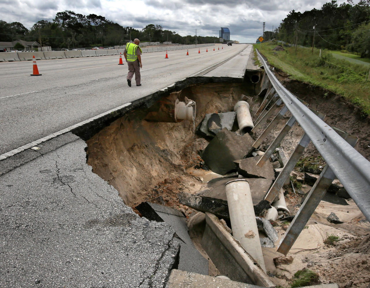 A Florida Highway Patrol trooper inspects a closed segment of Interstate 4, near State Road 434, in Longwood, Fla. on Monday, Sept. 11, 2017, after a portion of the interstate highway northeast of Orlando washed away during Hurricane Irma's passing through central Florida on Sunday night.  (Joe Burbank/Orlando Sentinel/TNS)